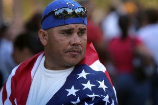 Un inmigrante arropado con una bandera de Estados Unidos durante una mar...