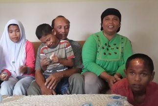 Septi Rangkuti carga a su hijo. Su esposa Jamaliah está detrás de Arif P...