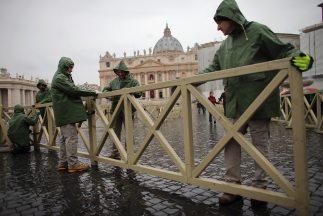 Trabajadores instalan vallas en la Plaza de San Pedro, escenario donde e...
