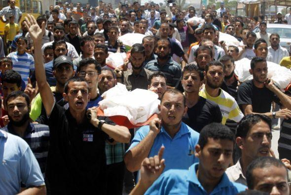 Familiares y amigos de   la familia   al-  Hajj   llevan   los cuerpos d...