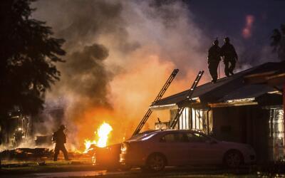 Los bomberos trabajan en la extición del incendio y al bús...