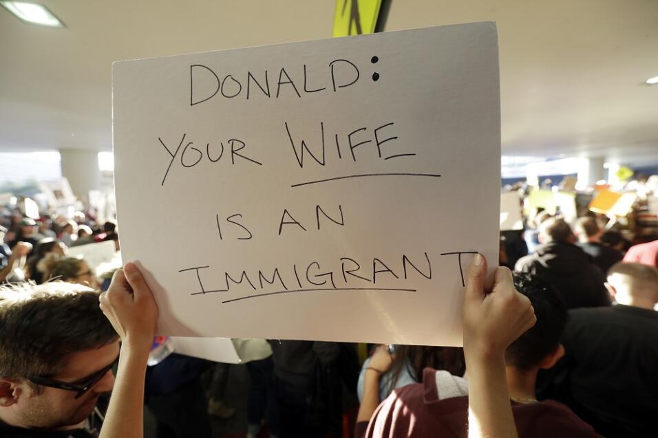 """Una persona levanta un cartel donde se lee """"Donald: tu mujer es una..."""