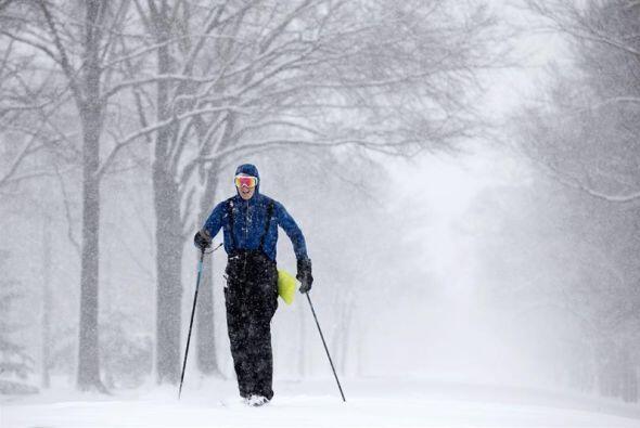 Un hombre esquía en un parque durante una tormenta de nieve en Washingto...