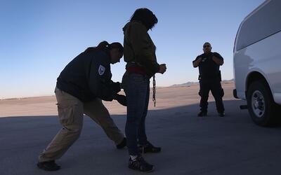 En esta foto de 2013, una agente de seguridad registra a una inmigrante...