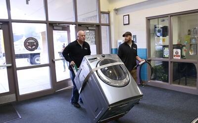 Trabajadores de la empresa Whirlpool hacen una entrega en una escuela in...