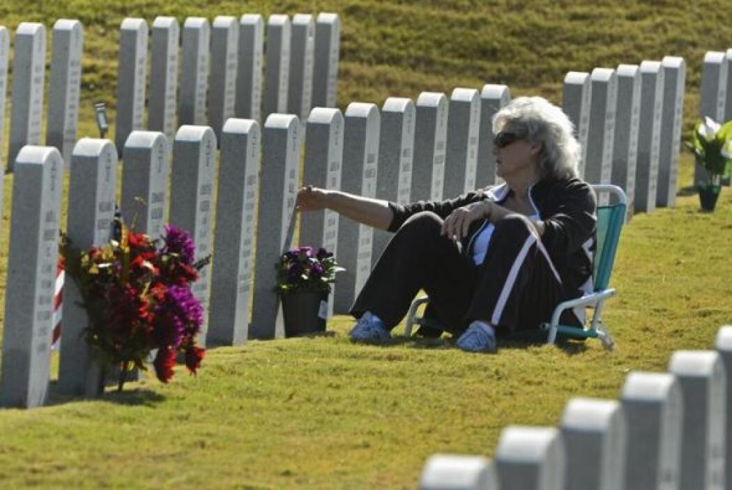 Rosie Smith toca la tumba de su esposo de 48 años, Jack Smith.