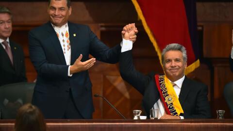 El presidente saliente, Rafael Correa, alza la mano del nuevo presidente...
