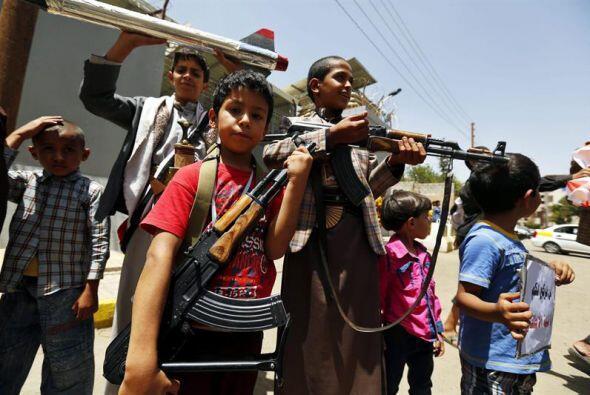 Varios niños yemeníes posan con armas durante una protesta en contra de...