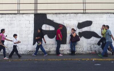 Peatones en Caracas caminan bajo la atenta mirada del ex presidente.