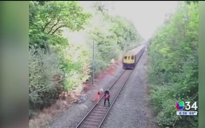 Hombre rescata a un ciclista de ser arrollado por un tren