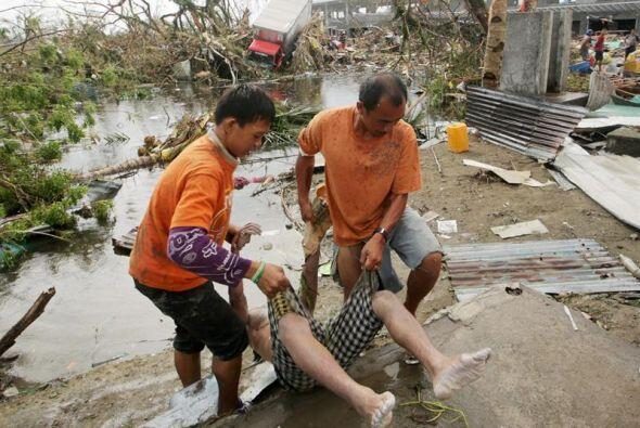 Filipinos cargan a una víctima del supertifón Haiyan que devastó su país...