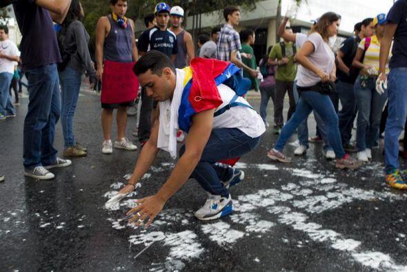 Un hombre pinta manos blancas en el piso durante una protesta contra el...