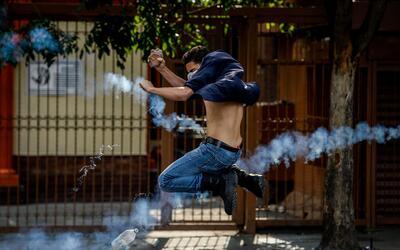 Un joven manifestante trata de esquivar una bomba lacrimógena arr...