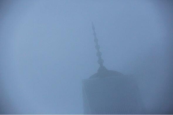 El One World Trade Center se ve a través de nubes bajas, mientras que lo...