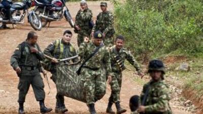 Soldados colombianos levantan el cuerpo de uno de sus 11 compañeros fall...