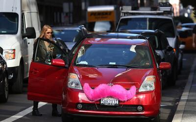 Un Toyota Prius con el distintivo bigote rosado de Lyft, recoge a una pa...