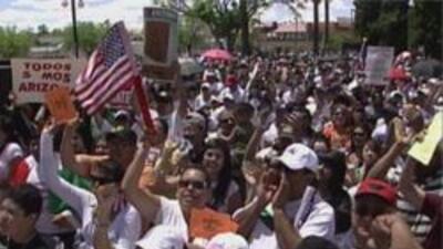 """Los manifestantes llevan el lema """"Todos Somos Arizona""""."""