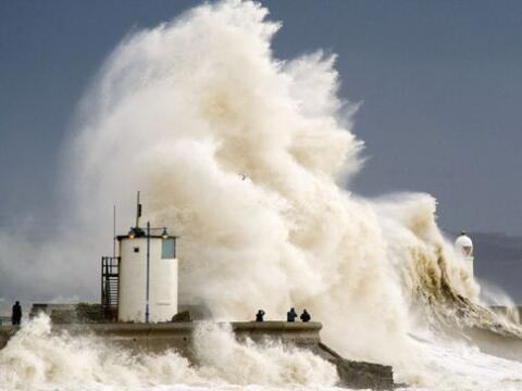 Espectadores ven cómo las olas rompen sobre la pared del puerto en Porth...