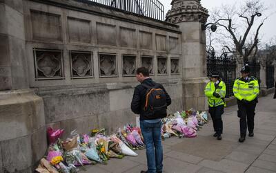 Un transeúnte se detiene delante de las flores depositadas en la...