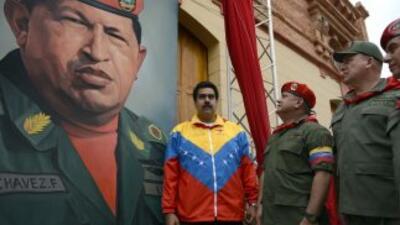 Nicolás Maduro con la imagen de Hugo Chávez de fondo.