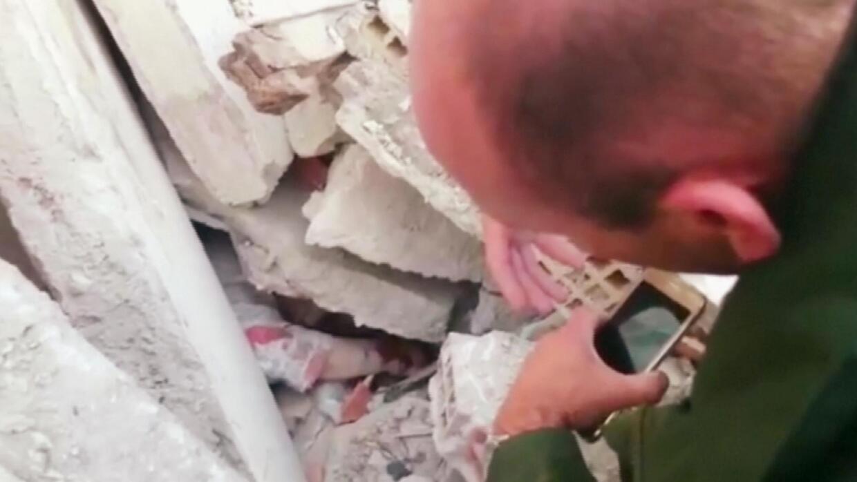 Bajo los escombros, un oficial consuela a un sobreviviente del terremoto...