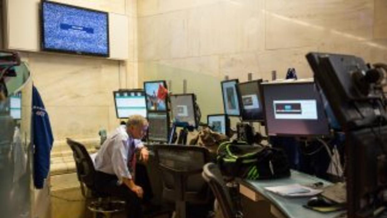 Un comerciante trabaja en el piso de la Bolsa de Valores de NY, cuando,...