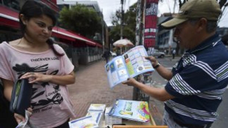 Un vendedor mostrando el álbum de Panini a una mujer en Colombia.