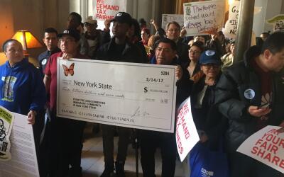 Miembros de la comunidad inmigrante cargan un cheque simbólico qu...