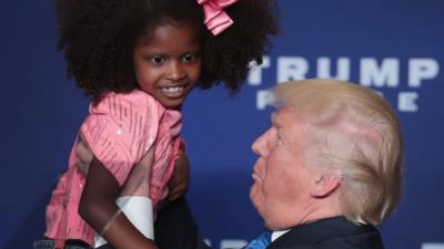El candidato presidencial republicano Donald Trump alza a una niña duran...