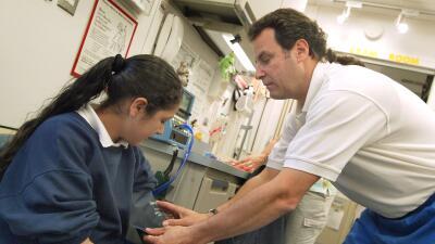 Un enfermero realiza un examen médico a una niña hispana en Cicero, Illi...