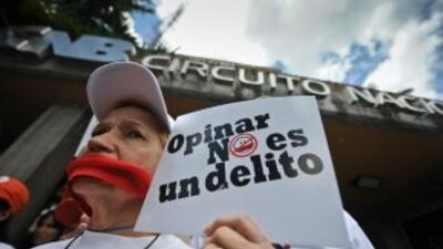 Una mujer protesta contra la censura impuesta por el gobierno de Chávez,...