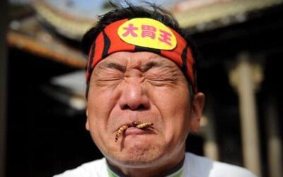 Pan Yizhong reacciona mientras come gusanos durante una carrera de comid...