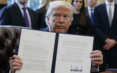 El presidente Donald Trump muestra la firma de la orden ejecutiva que em...