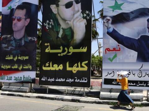 Una mujer camina en Damasco entre retratos del presidente sirio Bashar A...