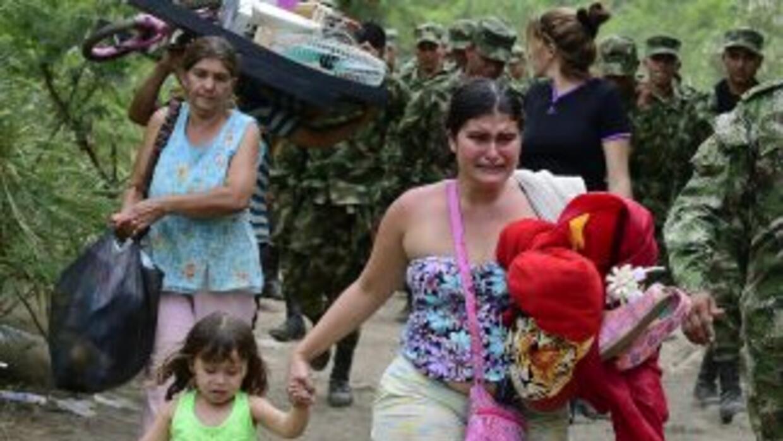 Una mujer colombiana, deportada desde Venezuela, cruza el paso fronteriz...