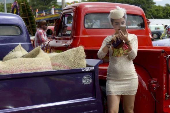 Una mujer toma fotos durante un desfile de coches clásicos en el...