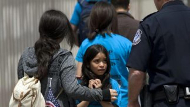 Mahalia Velazco (c), de 8 años, observa a un oficial estadounidense de f...