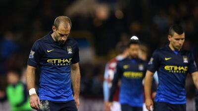 Los jugadores del Manchester City se retiran cabizabajos luego de su der...