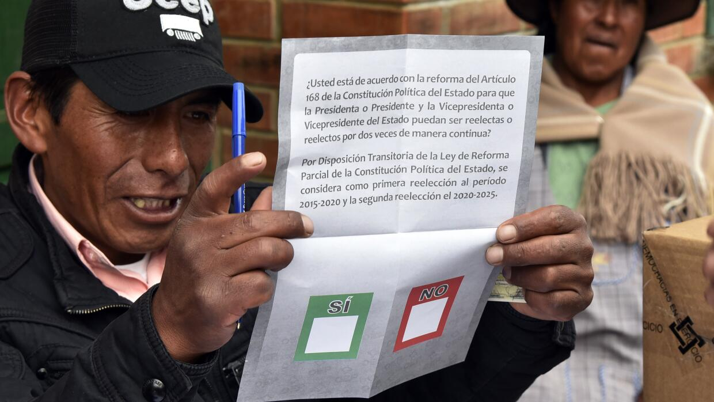 Un juez de la elección muestra la papeleta que usan los votantes.