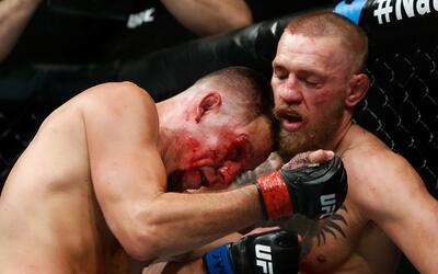 Nate Díaz, visiblemente golpeado, trata de acorralar a McGregor.