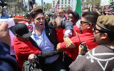 Un reportero es retenido en la protesta al mitin de Trump en San Diego.