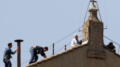 Trabajadores instalan la chimenea en el techo de la Capilla Sixtina por...