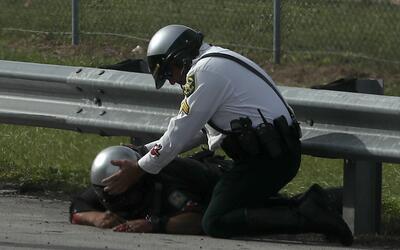 Compañeros de la uniformada ayudan al policía accidentado...