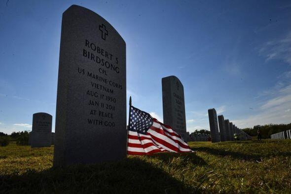 Vista de una pequeña bandera estadounidense puesta en una tumba d...