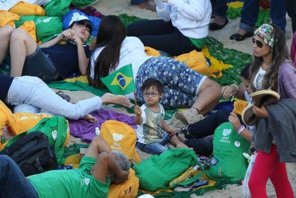 Cansados, los peregrinos aguardan la llegada del Papa Francisco a la pla...