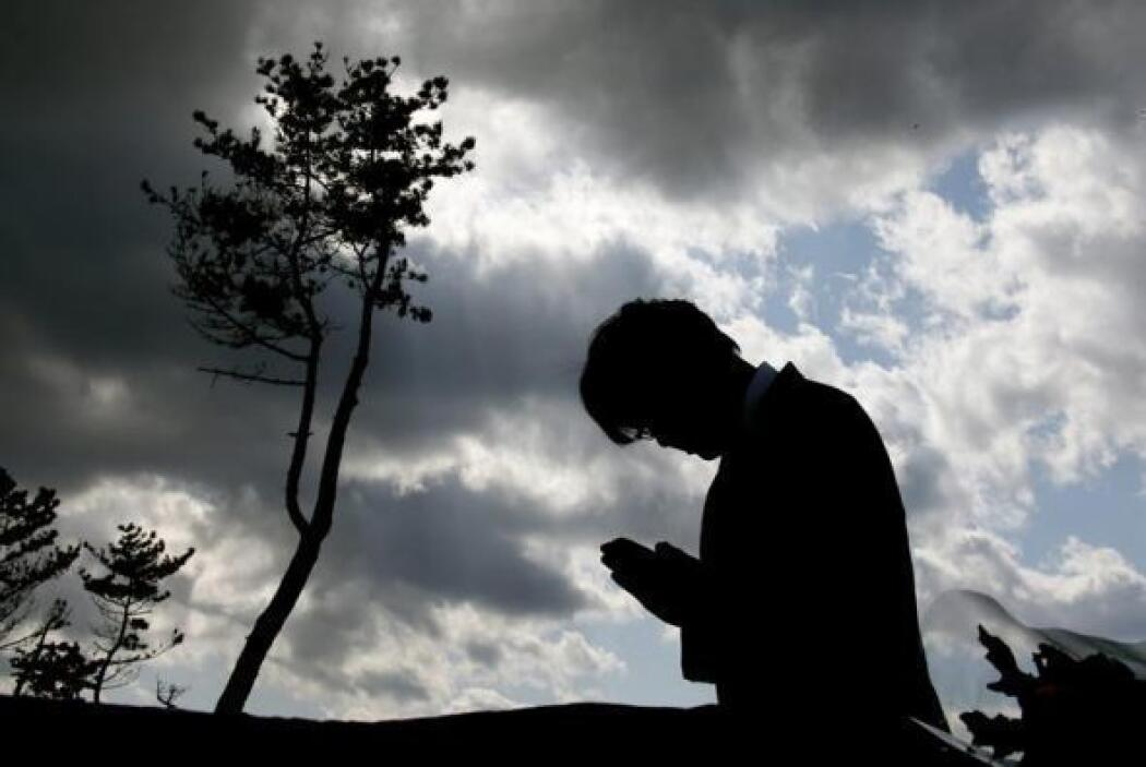 Una persona reza por las víctimas del mayor terremoto de la historia de...