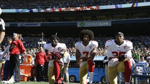 Colin Kaepernick (centro) inició con las protestas en la NFL.