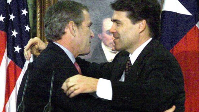 Rick Perry recibe un abrazo del presidente electo George W. Bush, quien...