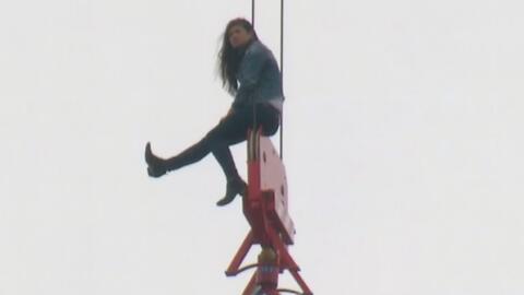 Rescatan a una joven que estaba sentada en la polea de una grúa a 100 pi...