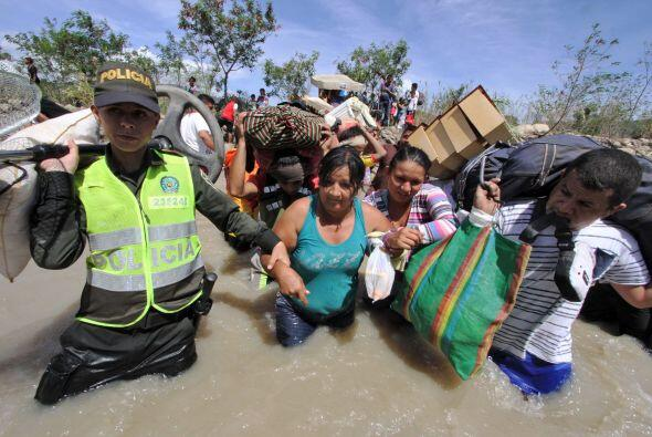 La policía colombiana ayudan a las mujeres colombianas llevan sus perten...